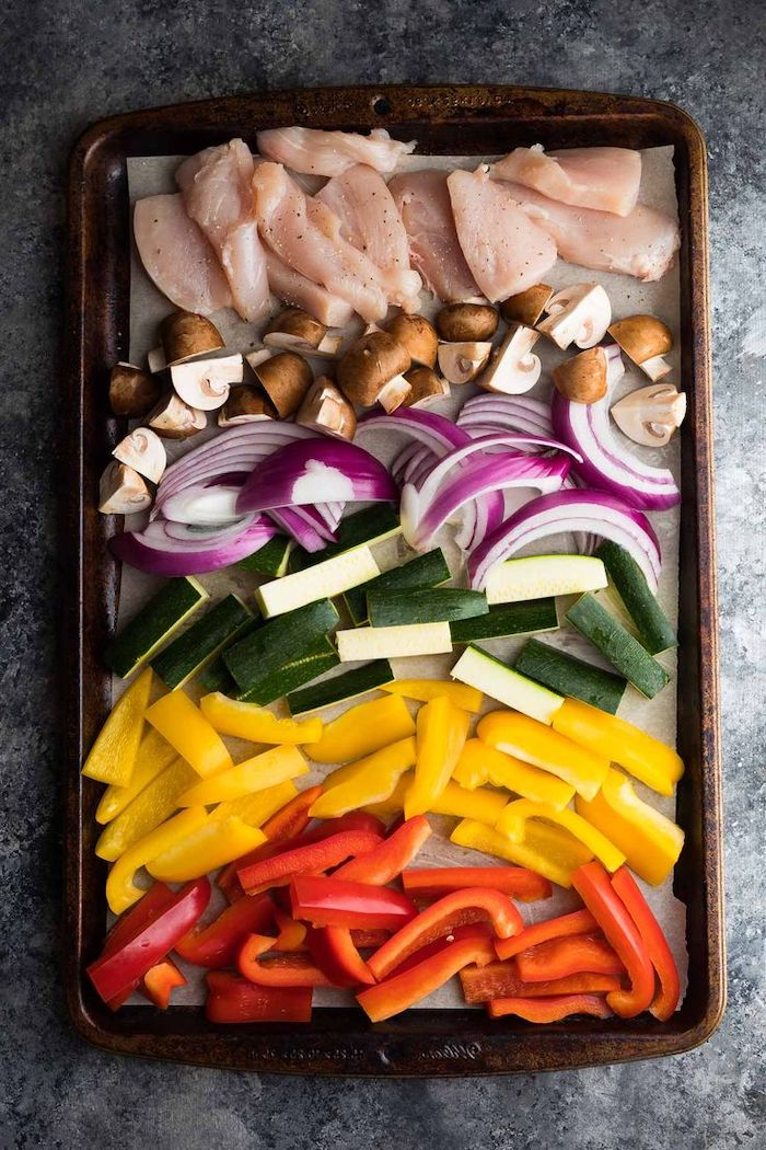 chicken fillet, mushrooms and onion, zucchini and peppers, arranged on a pan, healthy meal prep