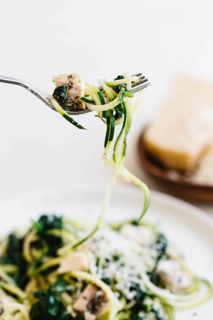 zucchini noodles, with chicken fillet, spinach and parmesan, blurred background, silver fork