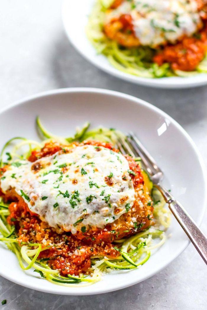 chicken parmesan, tomato sauce, zucchini noodles recipe, white plate, silver fork, white countertop