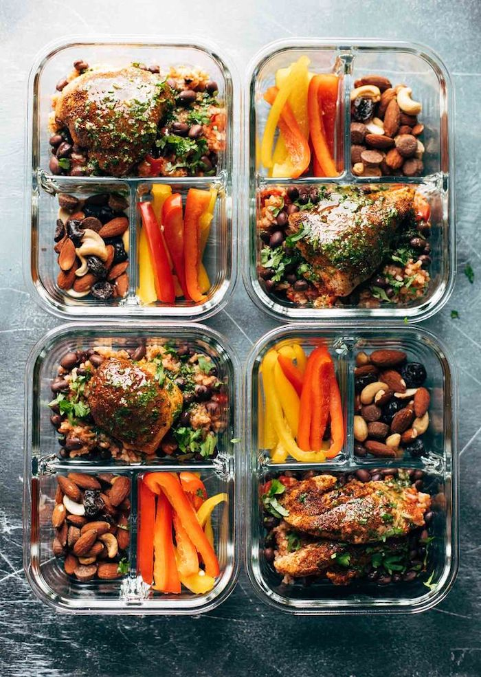 four glass containers, chicken fillet, peppers and nuts on the side, black wooden table, healthy meal prep ideas