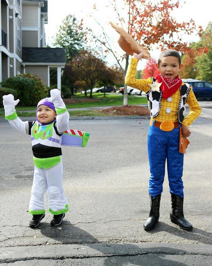 two boys, one dressed as woody, one dressed as buzz lightyear, toddler halloween costumes, toy story inspired