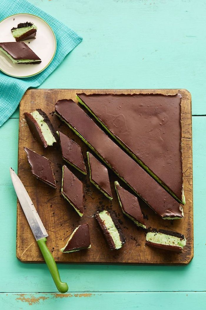 chocolate cake, mint mousse, cut into pieces, no bake desserts, on a wooden cutting board, turquoise wooden table