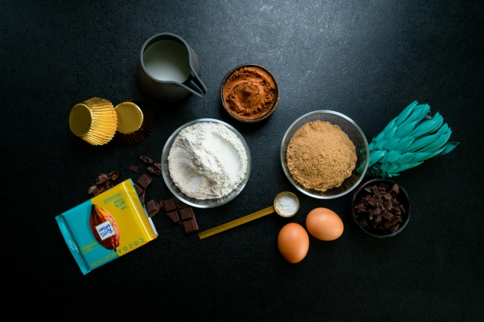cocoa and flour, eggs and milk, different ingredients, arranged on black countertop, chocolate cupcakes