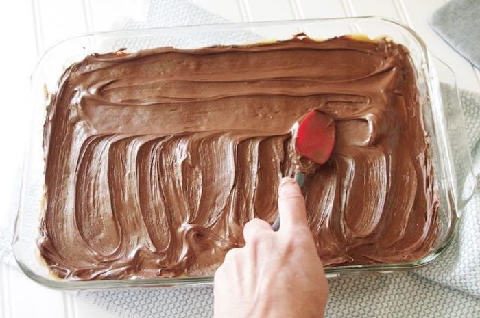 chocolate spread in a glass tray, quick easy desserts, red spatula, white wooden table