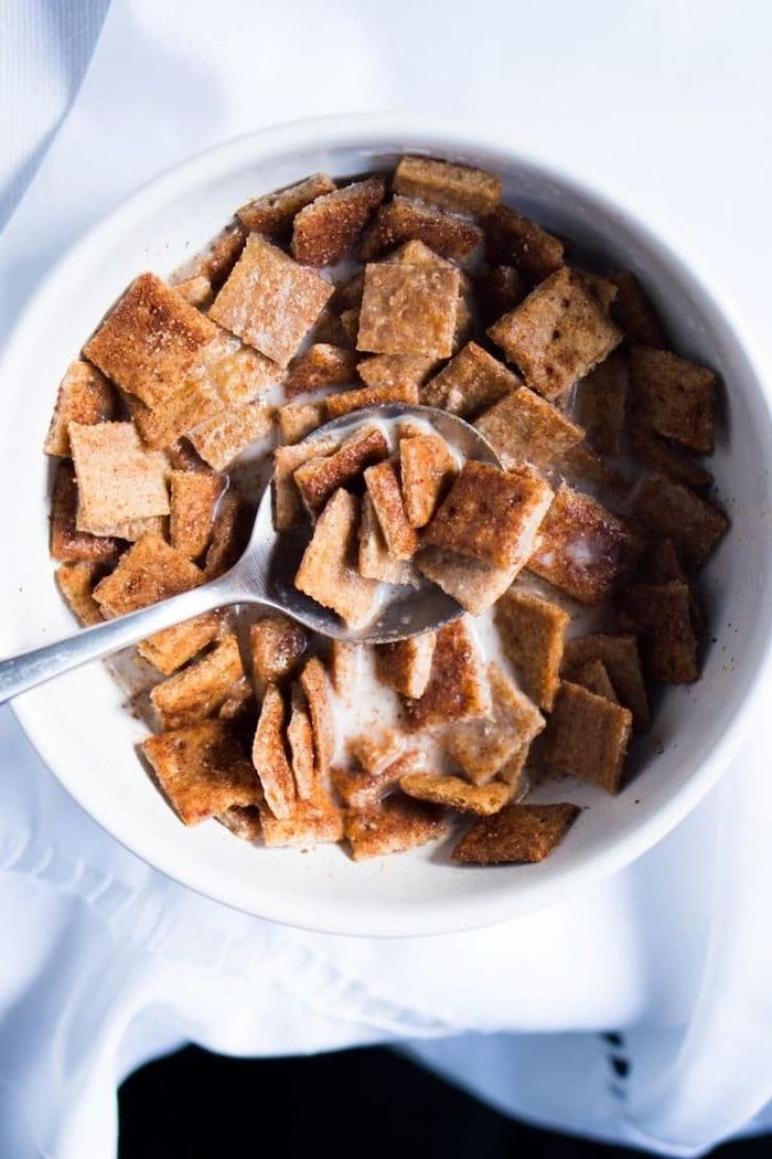 cinnamon toast crunch, soaked in milk, in a white bowl, with silver spoon, keto breakfast ideas, white table cloth