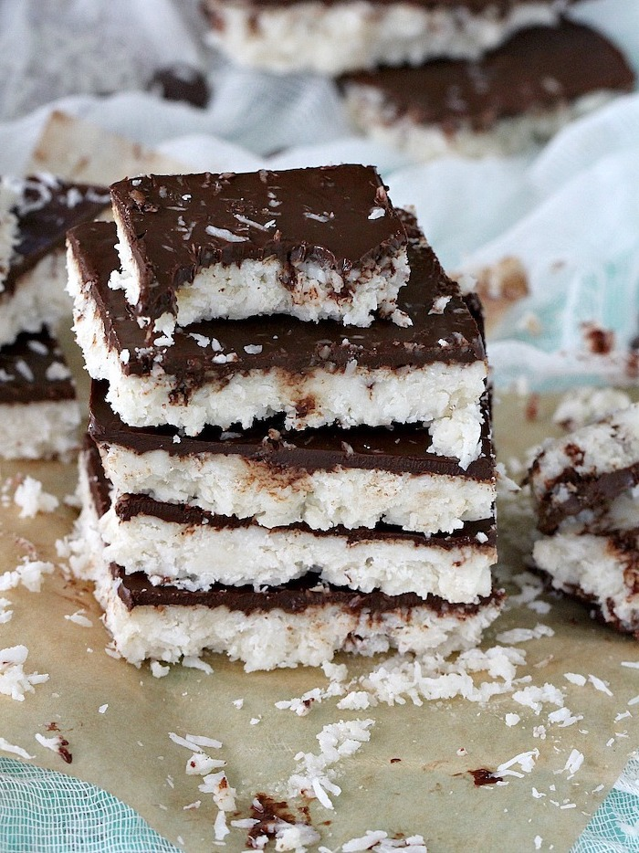 easy no bake desserts, coconut chocolate bars, one on top of the other, baking paper sheet, coconut flakes