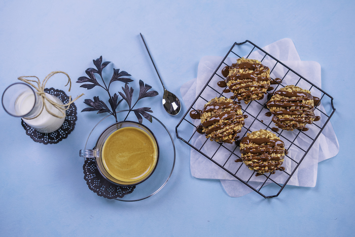 coffee cup, jar of milk, oatmeal cookies, chocolate on top, on a blue table, chocolate chip cookie recipe