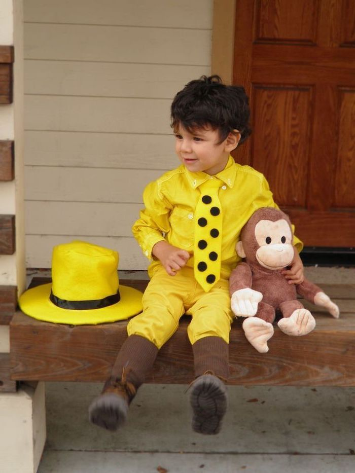 little boy, sitting on a step, dressed as the man in the yellow hat, carrying curious george, plush toy, halloween costumes for kids