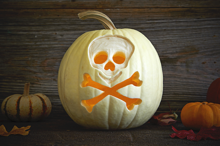 white pumpkin, skull carved into it, pumpkin carving ideas, wooden background, lit by candles