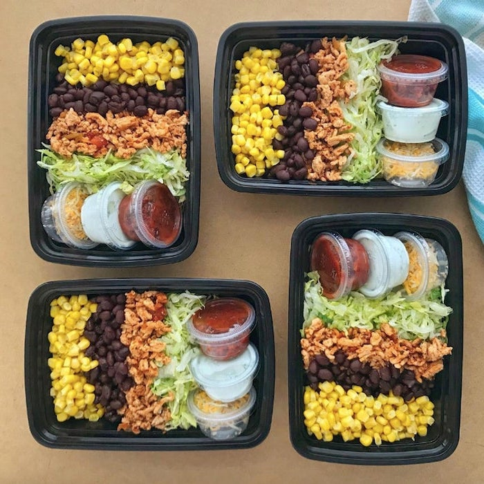 four black, plastic containers, easy healthy lunch ideas, corn and meat, black beans, green salad, sauces and cheese