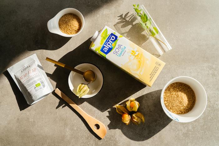 vanilla soya milk and cane sugar, agar agar and wooden spatula, creme caramel recipe, ingredients arranged on grey surface
