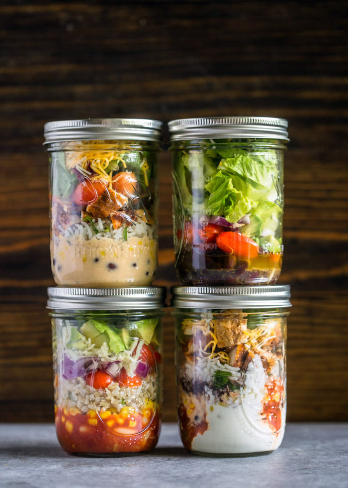 four mason jars, filled with different salads, easy healthy lunch ideas, wooden background, granite countertop