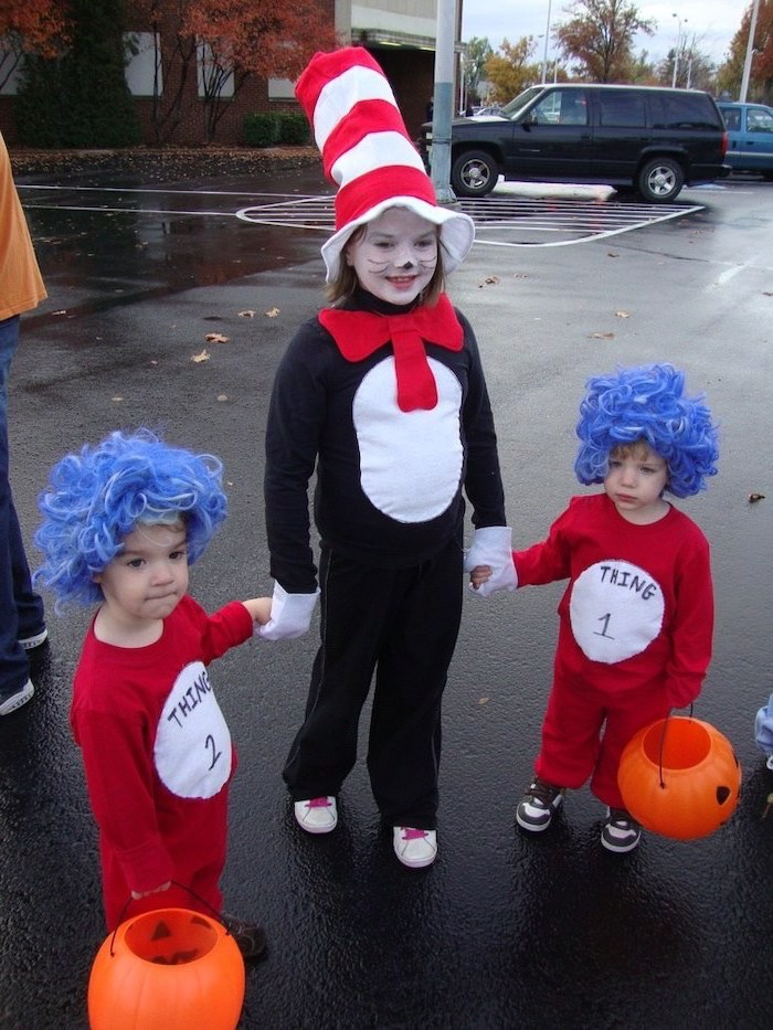 girl dressed as dr seuss, toddlers dressed as thing 1 and thing 2, toddler boy costume, standing on a parking lot