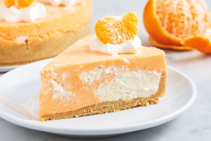 orange cheesecake, orange slice on top, easy summer desserts, on a white plate, white table