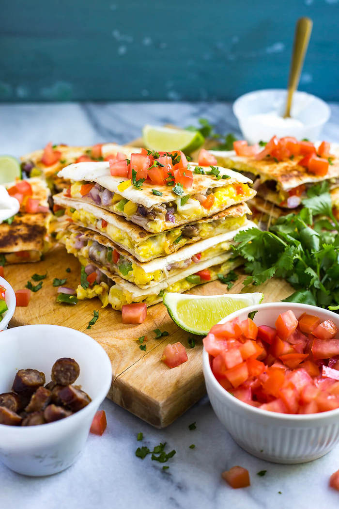 meal prep ideas, breakfast quesadillas, chopped tomatoes and sausages, in white bowls, wooden cutting board