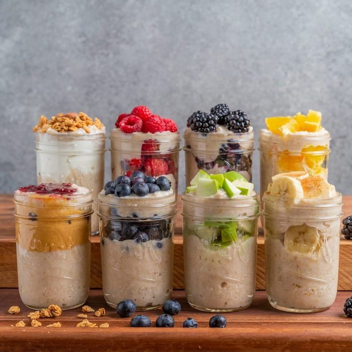 mason jars, filled with oatmeal and yoghurt, easy healthy lunch ideas, different fruits on top, berries and bananas, nuts and apples