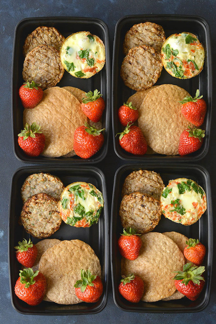 four black, plastic containers, healthy lunches for work, egg muffins, strawberries and pancakes