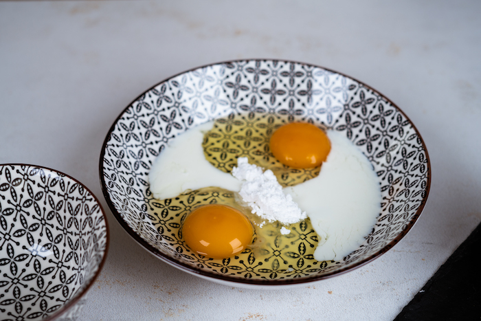 french toast recipe, two eggs and sugar mixed together in a black and white ceramic bowl, placed on white countertop