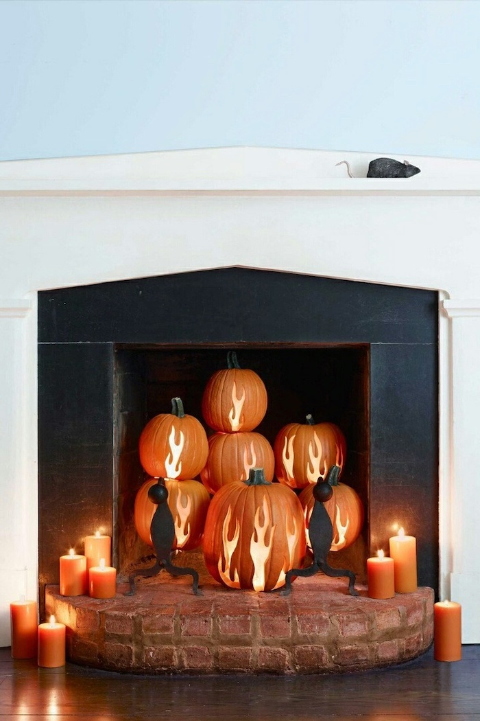 orange pumpkins, flames carved into them, pumpkin carving, arranged in a fireplace, lit by candles