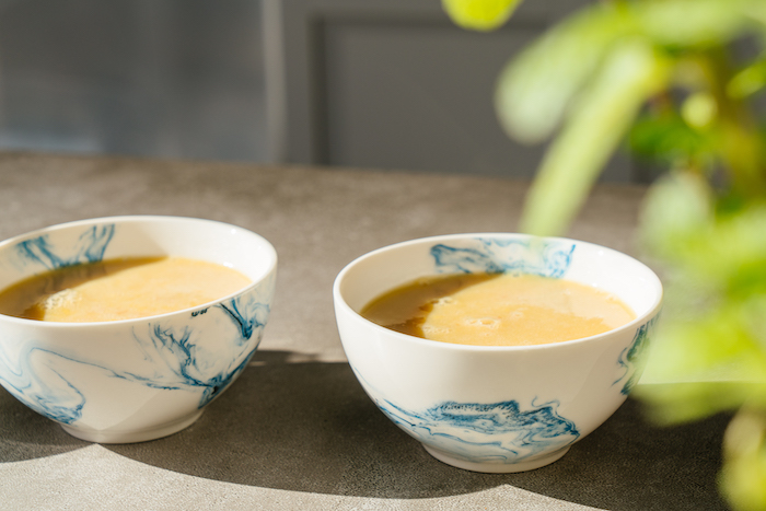 creme caramel, poured into ceramic white and blue small bowls, flan recipe, placed on grey surface
