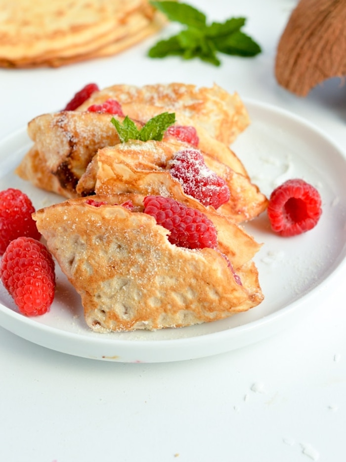 folded crepes, raspberries inside, keto diet recipes, raspberries in white plate, coconut flakes, powdered sugar