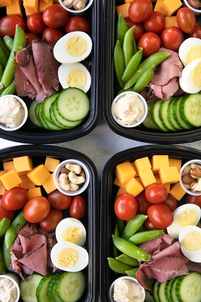 four black, plastic containers, healthy lunches for work, ham and cucumbers, cherry tomatoes, cheese and nuts inside
