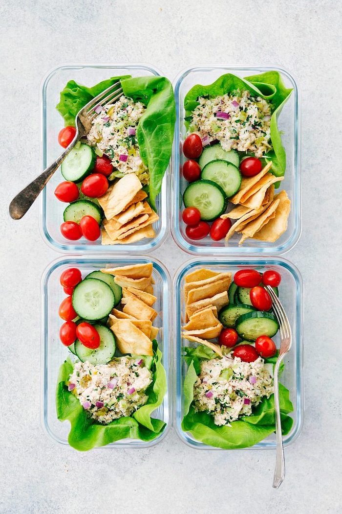 four glass containers, healthy lunches for work, tortillas and cucumbers, cherry tomatoes, green salad inside