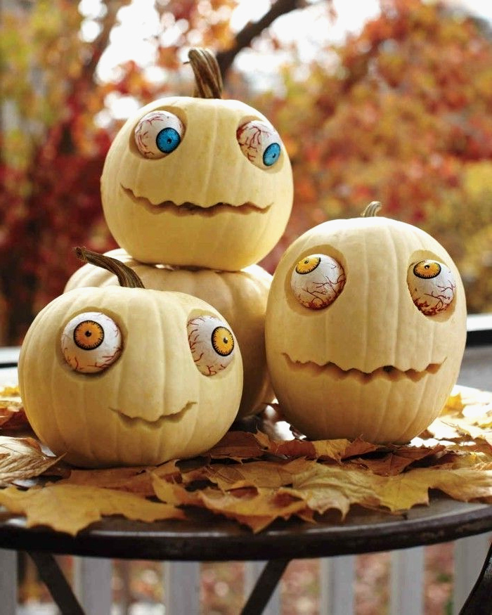 three white pumpkins, with large plastic eyes, pumpkin faces ideas, arranged on a black table, with fall leaves