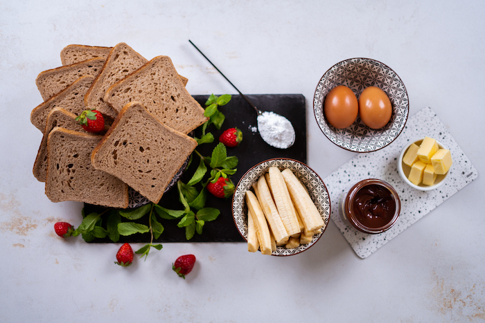 bread slices and strawberries, eggs bananas butter and chocolate in bowls, french toast, arranged on white countertop