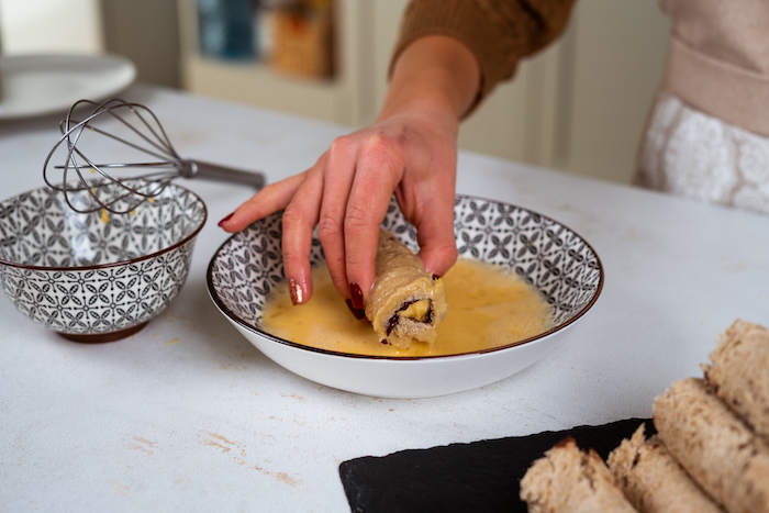 bread roll up with chocolate and banana inside, french toast recipe, dipped in beaten eggs in ceramic bowl