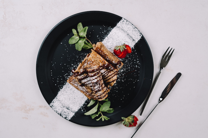 french toast, roll ups drizzled with chocolate, dusted with powdered sugar, strawberries on the side, placed on black plate