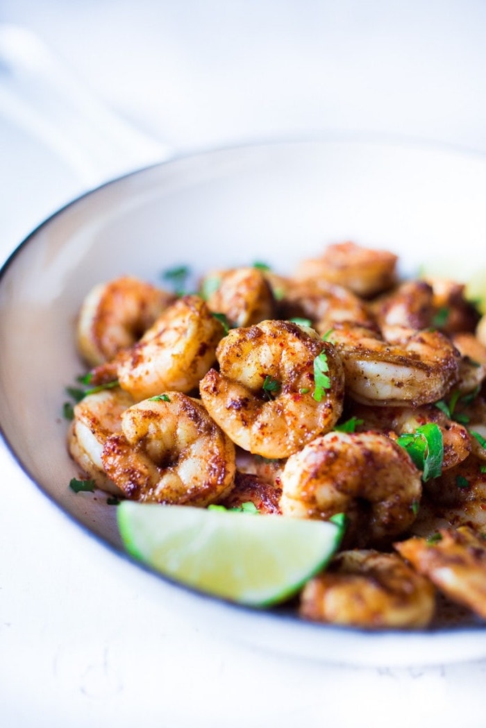white bowl, filled with fried shrimp, lime slice on top, taco toppings, white table