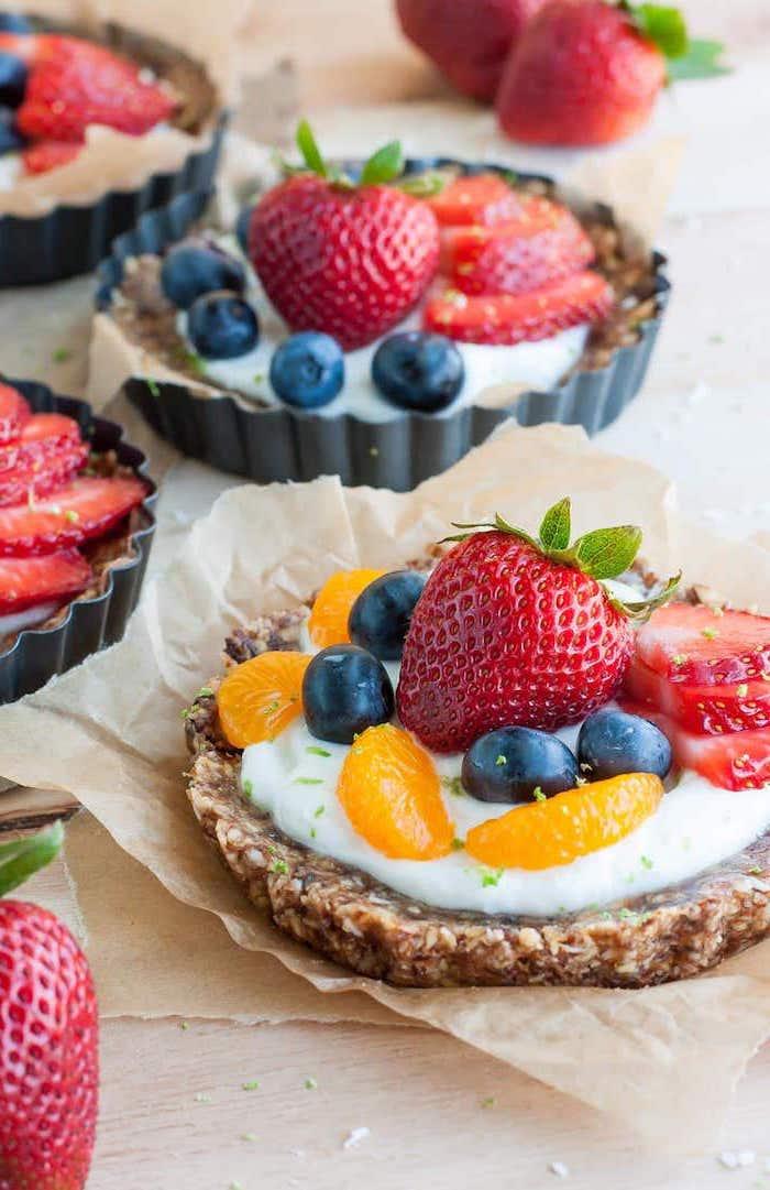 fruit yoghurt tart, easy summer desserts, blueberries and strawberries, orange slices, baking paper