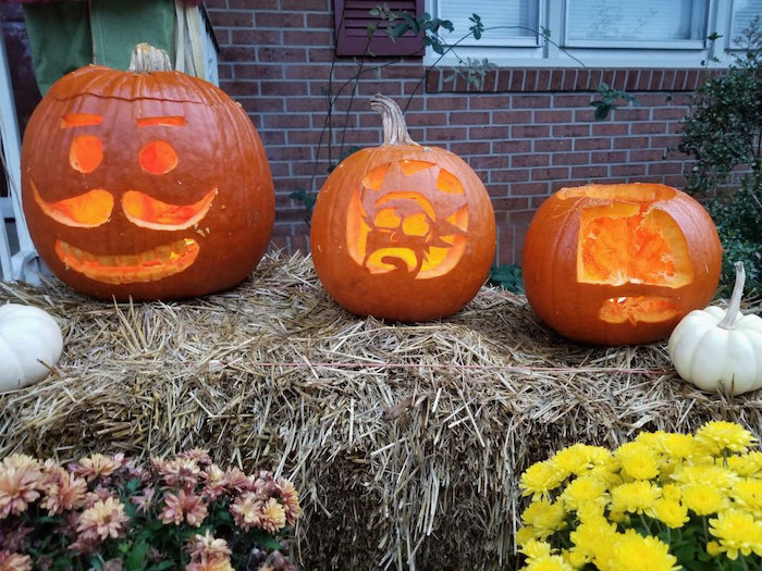 three pumpkins, arranged on a haystack, flowers around, brick wall, pumpkin faces ideas