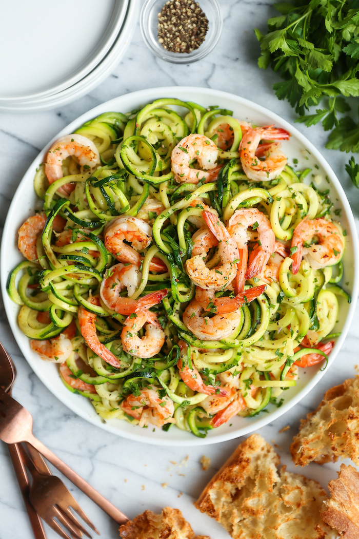 how to cook spiralized zucchini noodles, zoodles with shrimp, in a white plate, bruschetta on the side