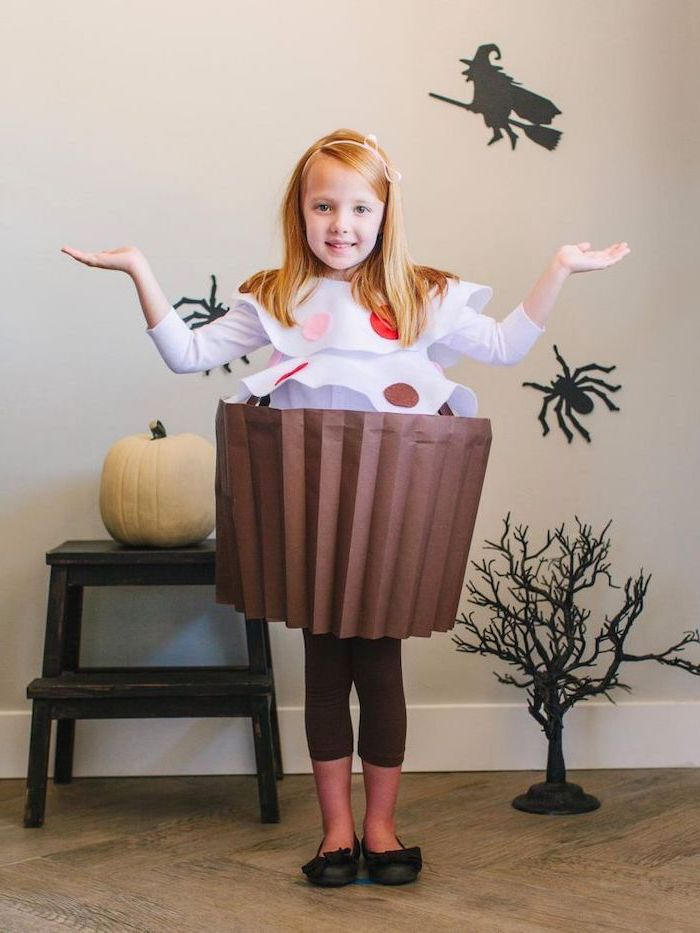 girl with blonde hair, dressed as a cupcake, made of paper, toddler girl costume, halloween decorations, in the background