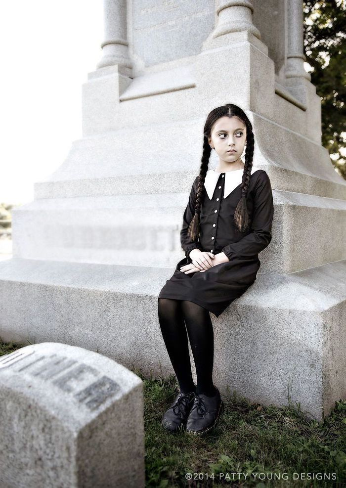 girl sitting on a tombstone, dressed as wednesday addams, halloween costume ideas, addams family inspired costume