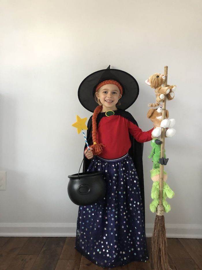 cool halloween costumes, girl dressed as witch, room on the broom character, plush cat toys, white wall