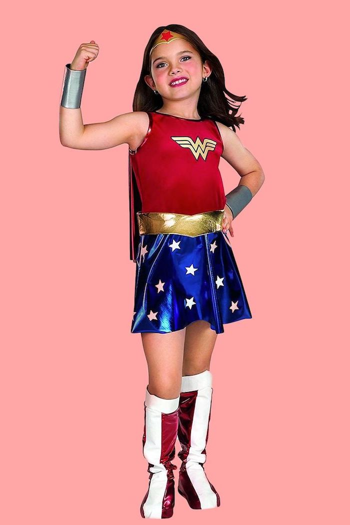 girl dressed as wonder woman, cool halloween costumes, red top, blue skirt, pink background