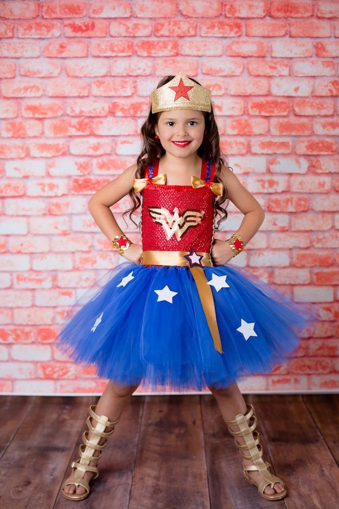 girl dressed as wonder woman, red top, blue tulle skirt, toddler boy halloween costumes, brick wall, gold gladiator sandals