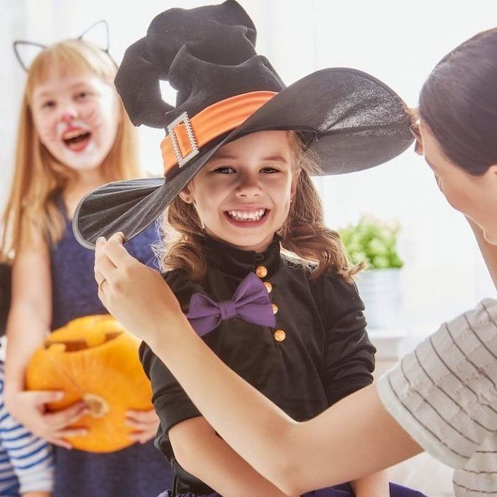 girl smiling, dressed as a witch, with large black hat, cute halloween costumes for girls, purple bowtie