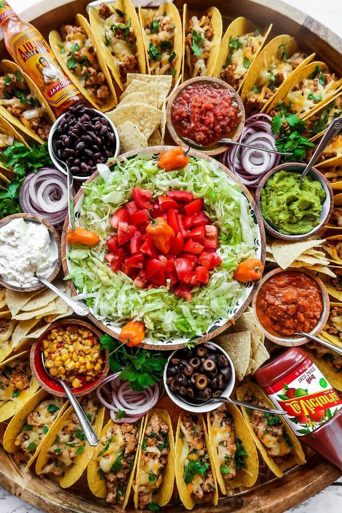 ground beef taco recipe, glass bowls, filled with different ingredients, mini tacos, arranged on a large, wooden tray
