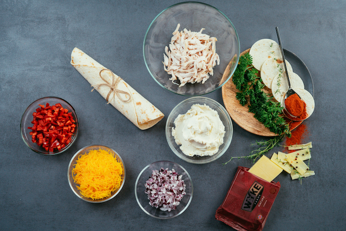 taco recipe, different ingredients, chopped in glass bowls, on black table, tortilla wraps, shredded cheese