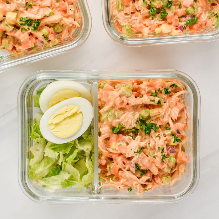 healthy meal prep ideas for weight loss, buffalo chicken salad, green salad, boiled egg, in a glass container