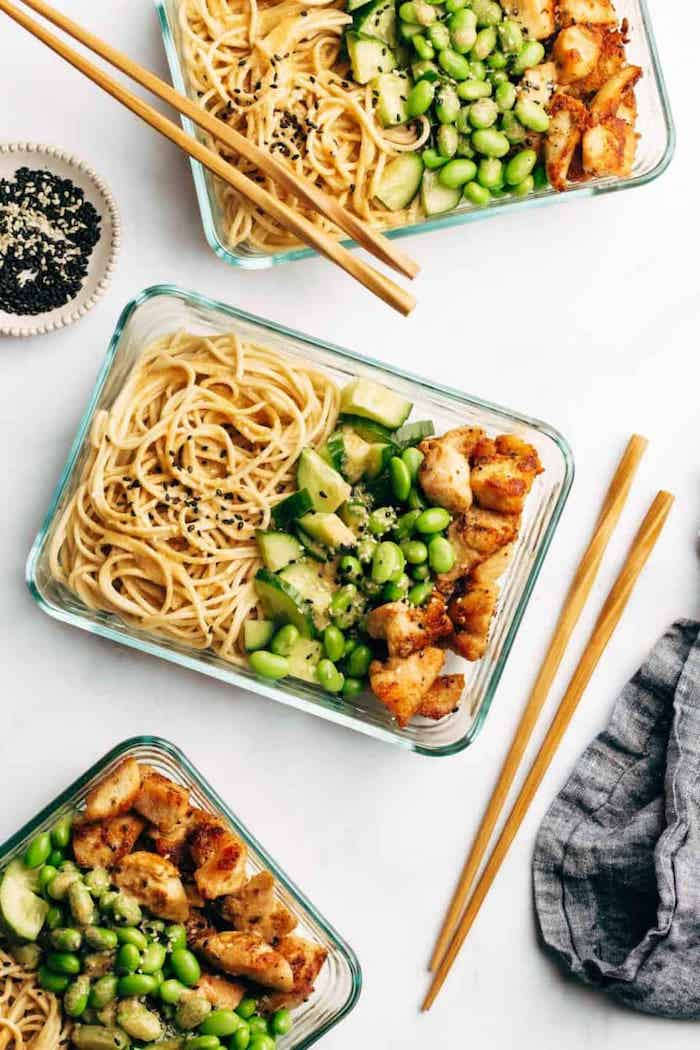 sesame noodles, healthy meal prep ideas, beans and cucumbers, chicken fillet, in glass containers