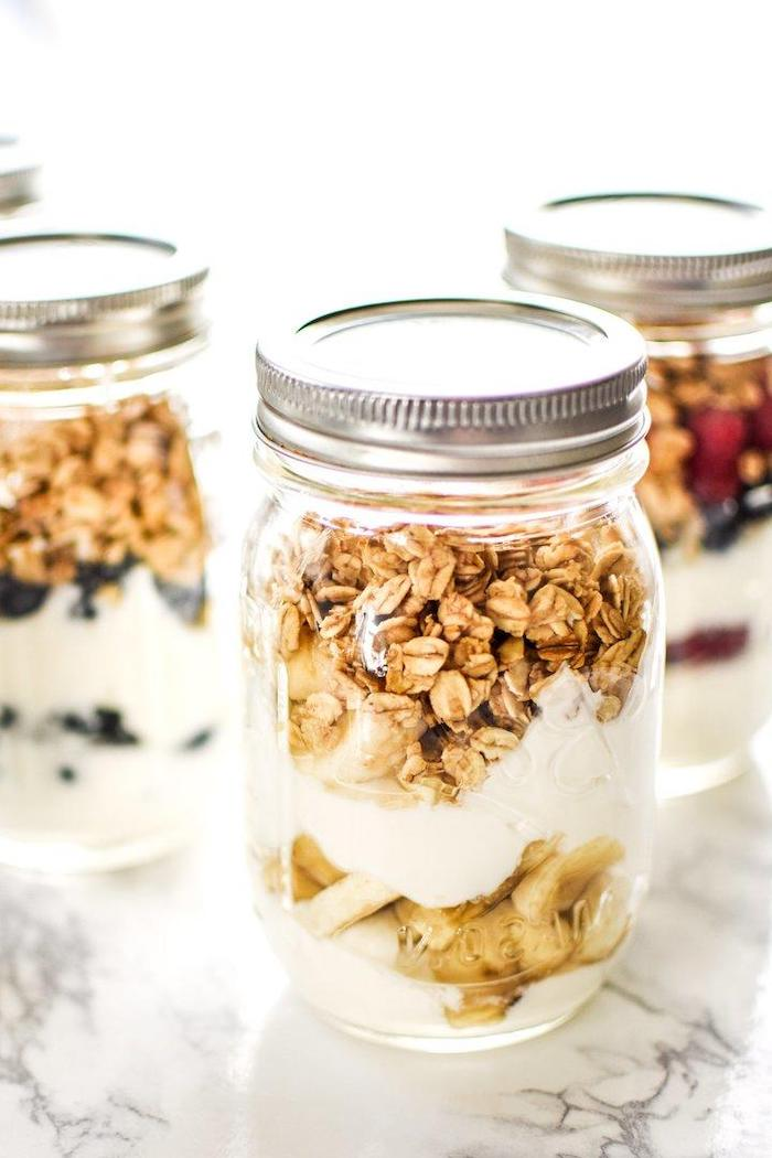 granola and yoghurt, inside mason jars, with different fruits, meal prep, marble countertop