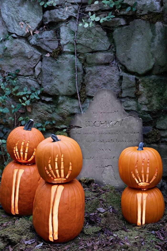 pumpkin carving, grave tombstone, large rocks, pumpkins with skeleton hands, carved into them