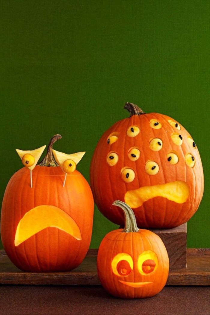 three pumpkins, with funny eyes, pumpkin faces ideas, arranged on a wooden crate, green wall