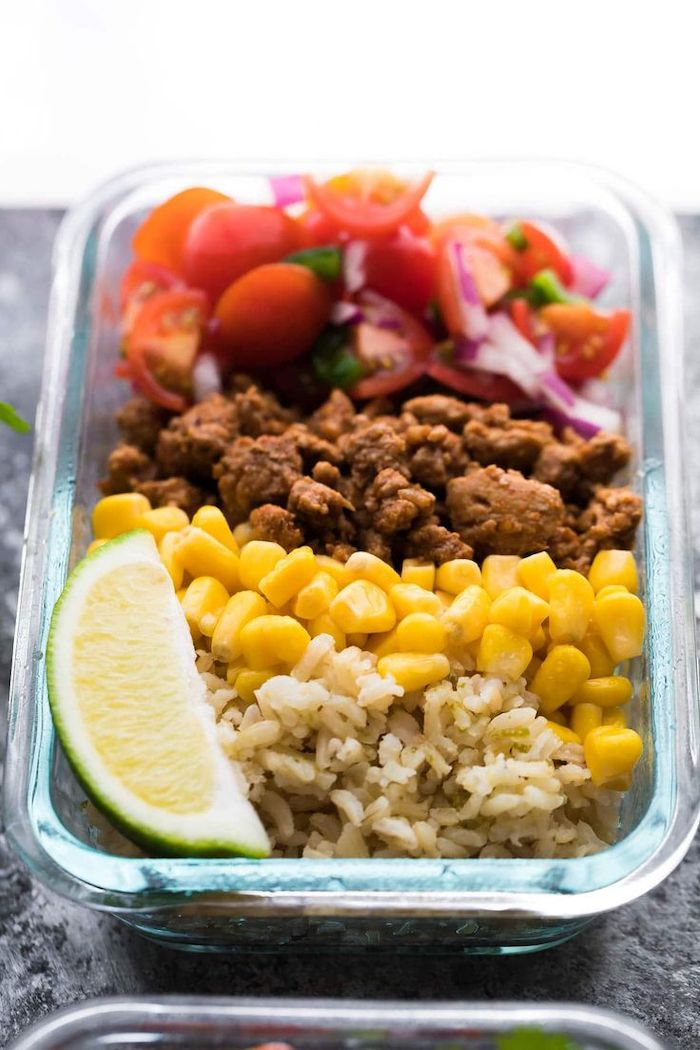 rice and corn, ground turkey, chopped tomatoes and onions, chicken meal prep, lime slice, in a glass container
