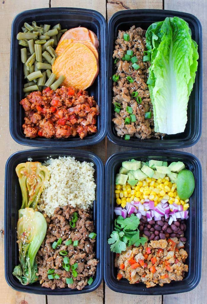 four plastic containers, with different meals inside, meal prep for the week, ground turkey, green salad